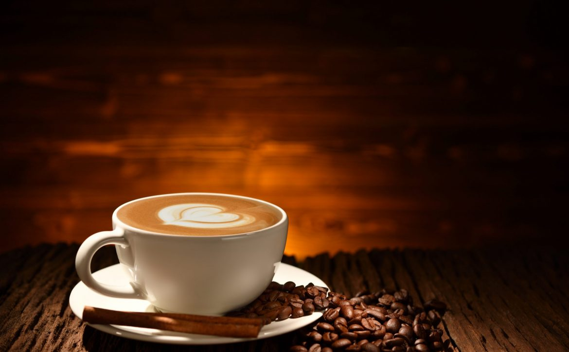 Cup of coffee latte and coffee beans on old wooden background