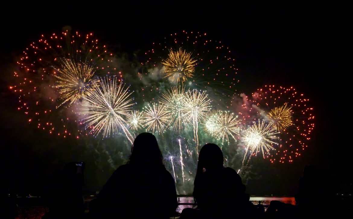 People watching beautiful fireworks together by the sea at night