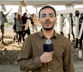 Young journalist speaking into microphone